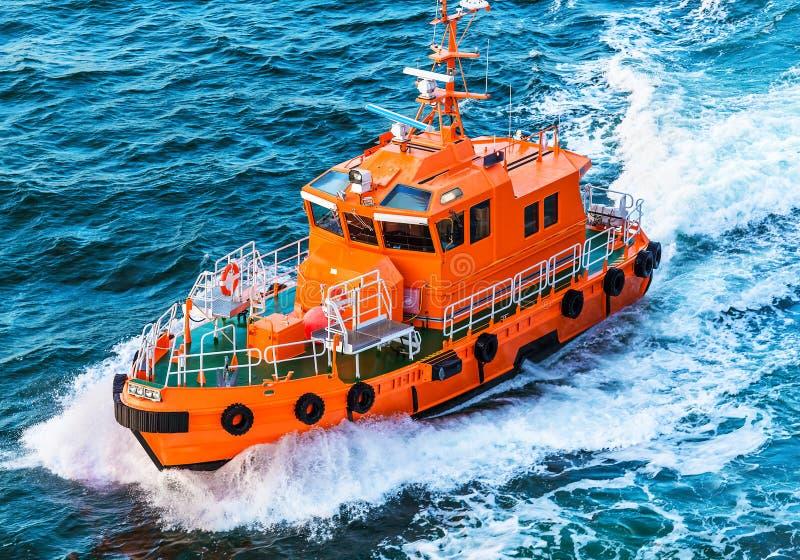 Rescue or coast guard patrol boat. Orange rescue or coast guard patrol boat industrial vessel in blue sea ocean water stock photos