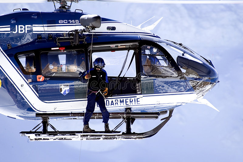 Rescue helicopter #1. A man stands on the skis of a helicopter in preparation for a rescue stock photography