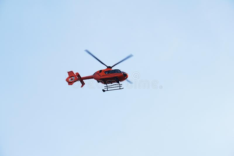 Rescue Helicopter or Air ambulance. Red air medical services heli copter midair against blue sky stock photography