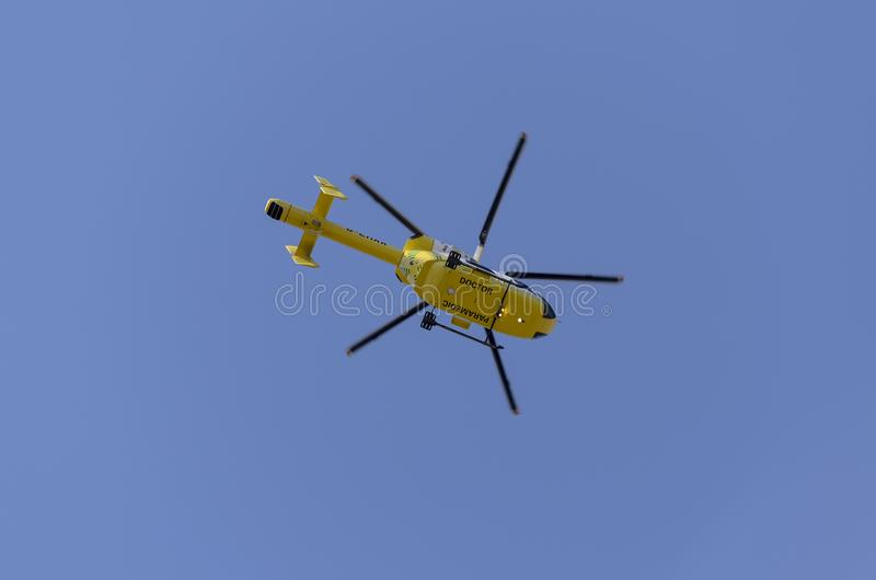 Rescue helicopter flying in a blue sky stock photo
