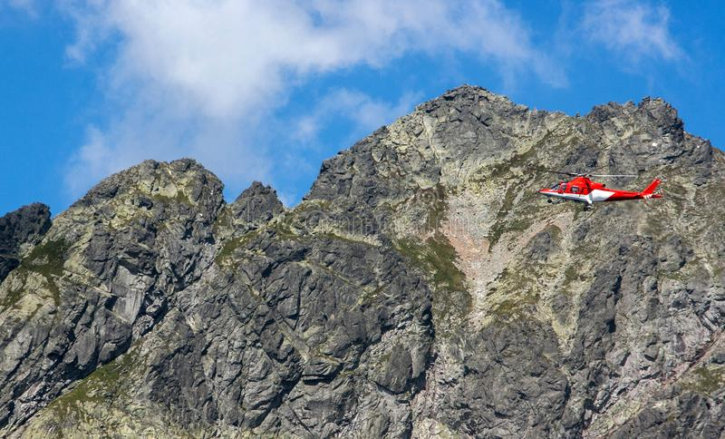 Rescue helicopter flying in the rocky mountains stock images