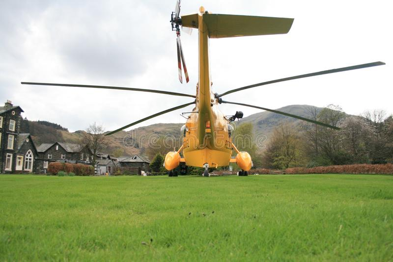 Rescue helicopter parked on a lawn - back view. RAF Rescue helicopter landed on the side of the lake, in Cumbria, as part of a training exercise. Huge rotor stock photos