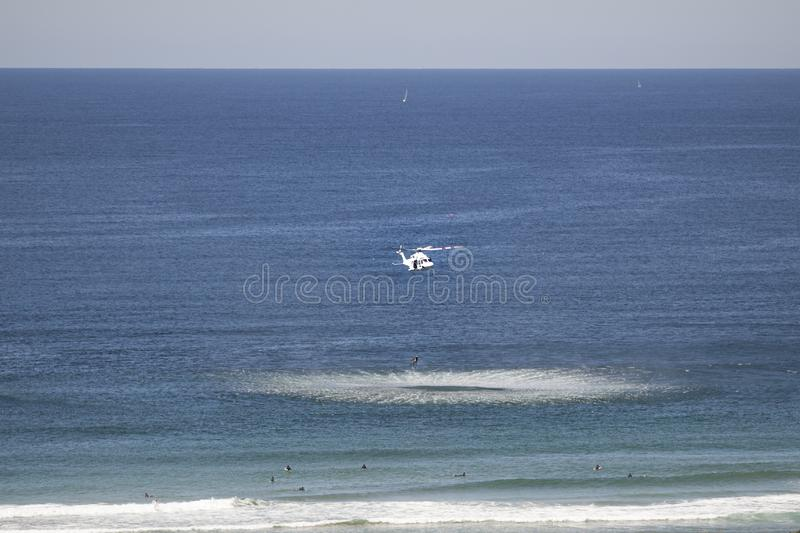 Rescue Helicopter pulling surfer up from ocean waves stock image
