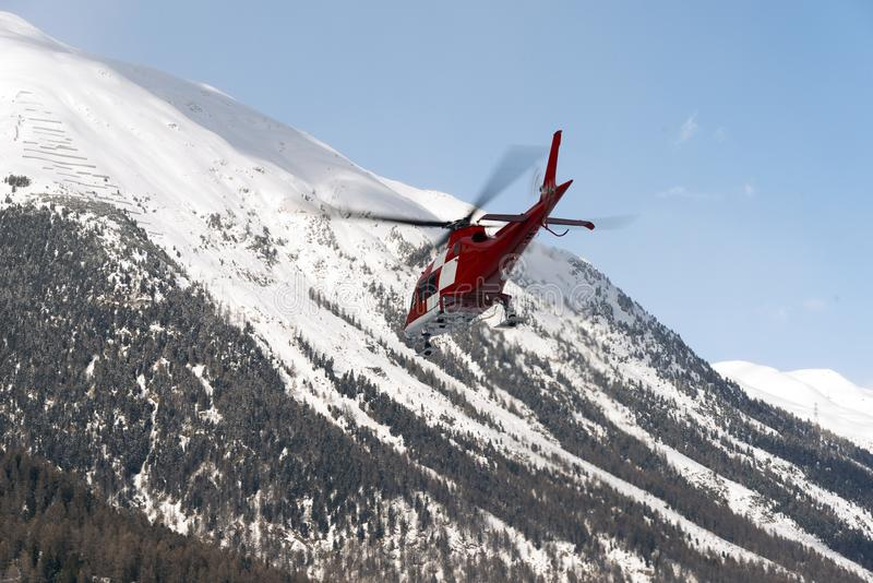 A rescue helicopter in the snowy alps switzerland in winter royalty free stock photos