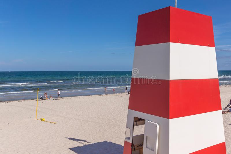 Rescue tower on the beach for the lifeguards. A red and white rescue tower with several stocks on the beach. Rorvig, Denmark, July 20, 2018 royalty free stock image