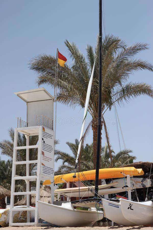 Rescue tower near the sailing boats parked against a palm tree royalty free stock photography