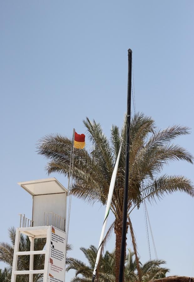 Rescue tower with red and orange flag against a palm tree stock image