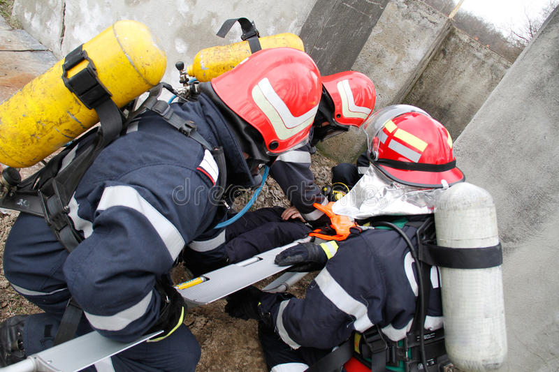 Rescue victim. Life savers rescue victim from damaged building royalty free stock image