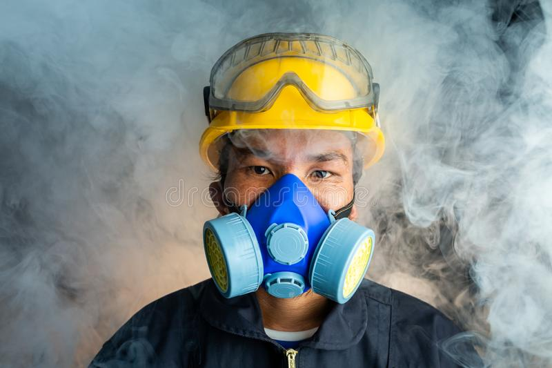 A rescue worker wears a respirator in a smokey, toxic atmosphere. Image show the importance of protection readiness and safety in. Industrial factory royalty free stock images