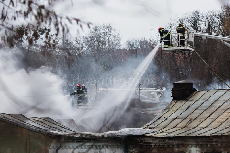 Rescuers firefighters extinguish a fire on the roof. The building after the fire stock photos