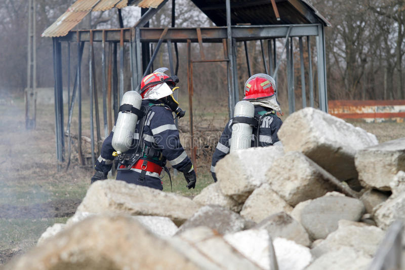 Rescuers. Life savers rescuers searching for victims of damaged building stock image