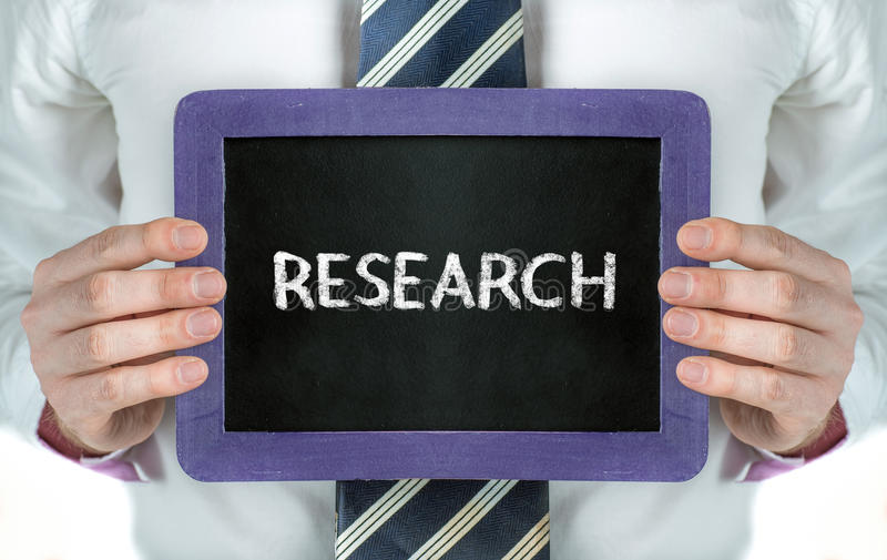 Research. Man holding blackboard with word Research royalty free stock image