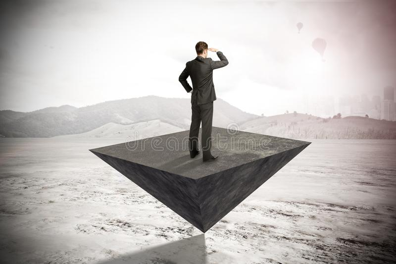 Research, balancing and success concept. Businessman looking into the distance while standing on abstract pyramid on blurry outdoor background. Research royalty free stock images
