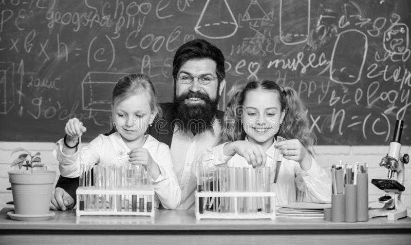Research studies. Science teacher and pupils doing research work. Teacher and primary school children holding test tubes royalty free stock image