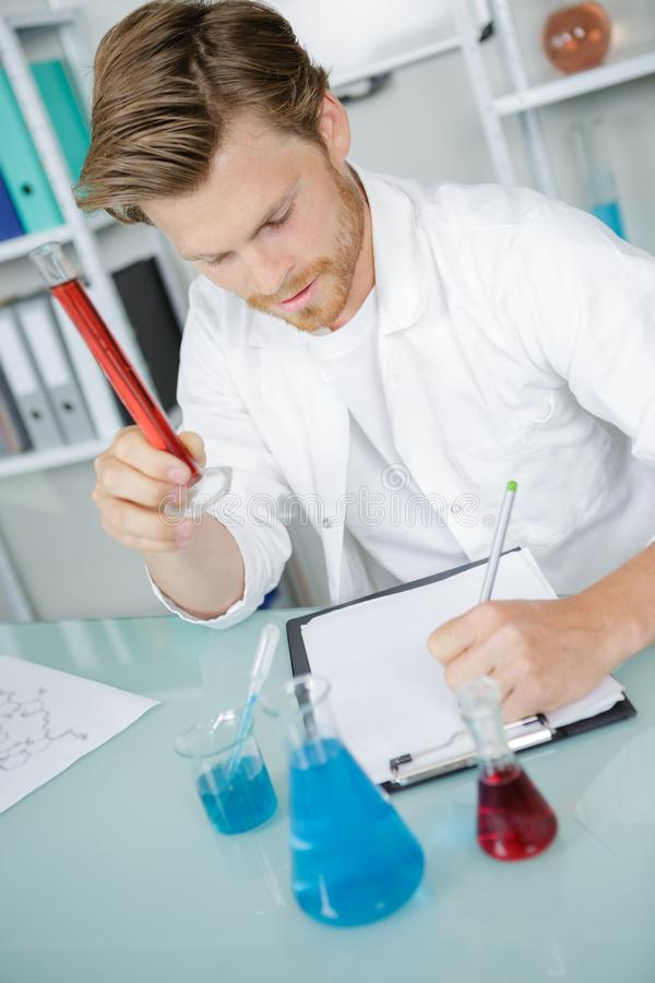 Research worker doing experiments with chemical liquid at laboratory stock images