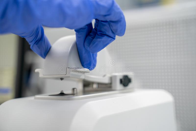 The researcher drops 2 micro-liters of the sample on pedestal to measures the RNA concentration and quality using the Nano Drop royalty free stock photos