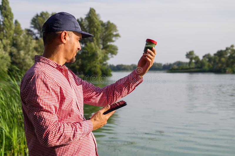 Researcher ecologist with tablet examines tube with green algae outside. Side view of researcher ecologist with tablet examines tube with green algae outside stock photos