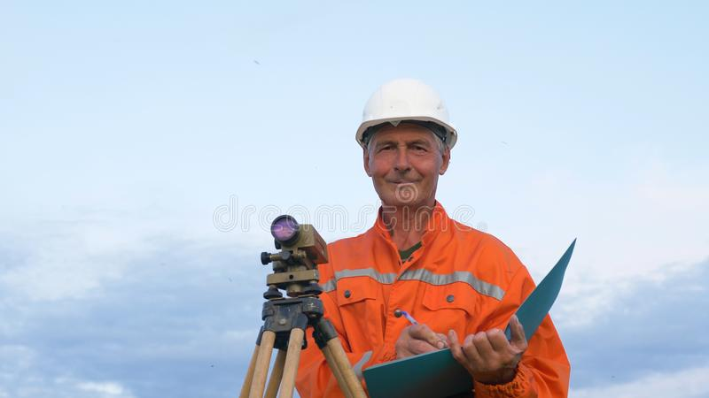 Researcher looks through level and writes in blue folder royalty free stock photo