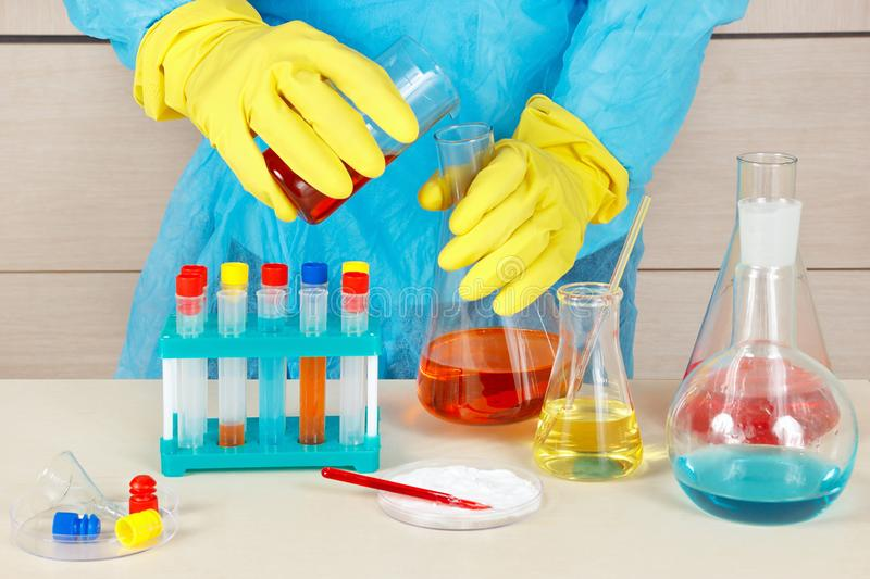 Researcher in rubber gloves engaged in chemical experiments in laboratory. Researcher in rubber gloves engaged in chemical experiments in the laboratory royalty free stock image