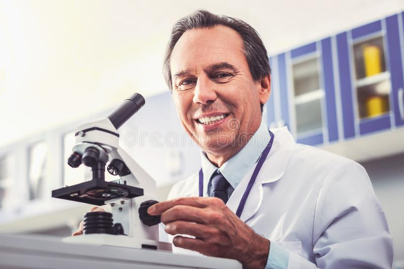 Researcher smiling while inventing new technology for microscope. New invention. Famous researcher smiling while inventing new technology for modern sensational royalty free stock image