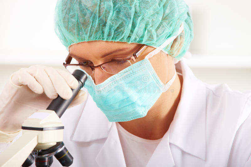 Researcher using a microscope in a laboratory. Scientific researcher using a microscope in a laboratory stock photography