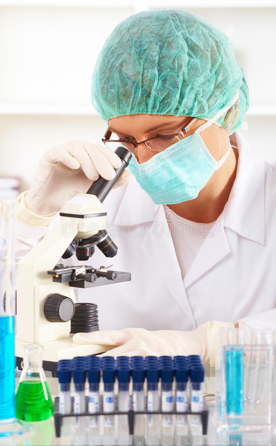 Researcher using a microscope in a laboratory. Scientific researcher using a microscope in a laboratory royalty free stock image