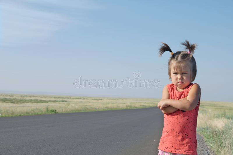 Resentful child is standing and don`t want to go anywhere defend own position . Little girl in kazakh steppe. Cute adorable kid. Relationships with kids royalty free stock photos