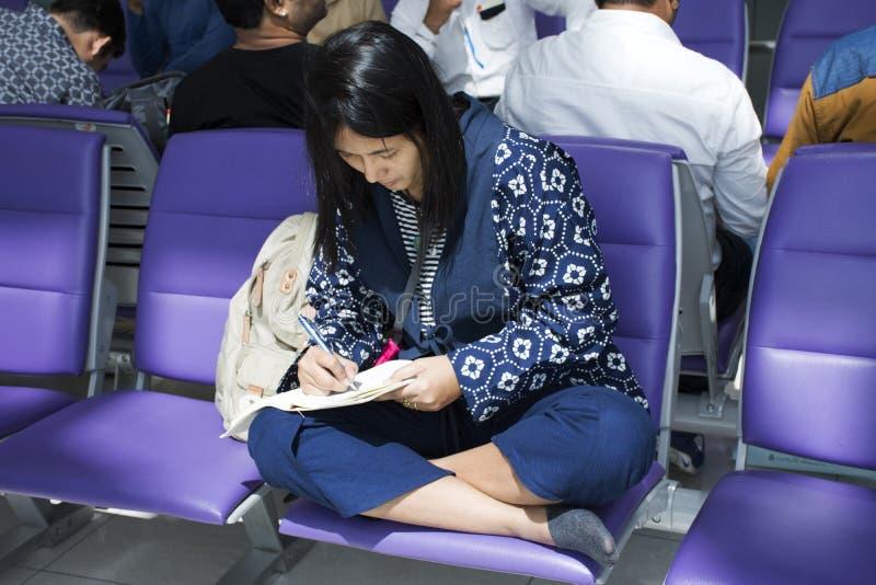 Reser thai kvinnor för den Asien handelsresanden med pennhandstilminnesmärken på anteckningsboken om resa royaltyfri bild