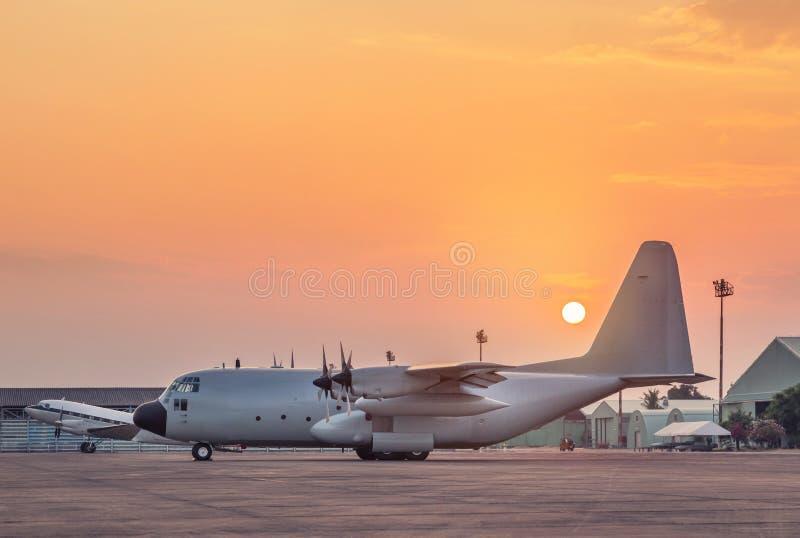 Reserv för last för transport som militärt parkerad flygplan är klar till starten på solnedgångtid arkivbilder