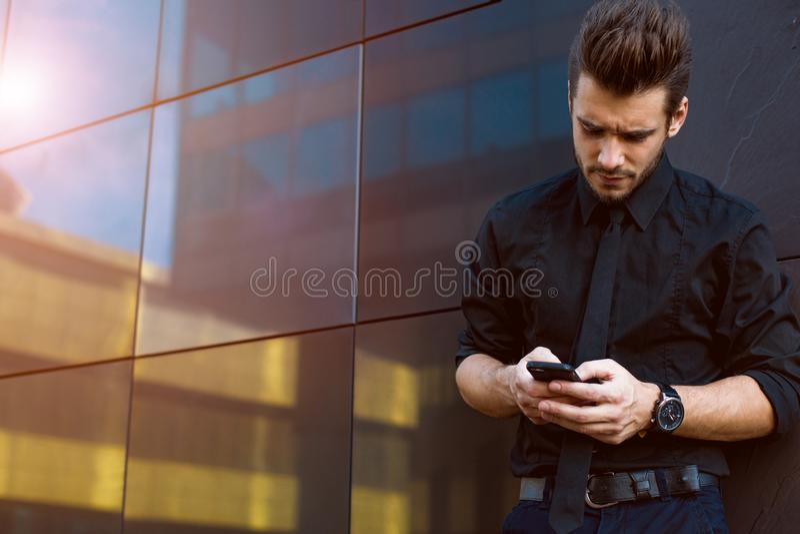 Reservación en línea del economista de sexo masculino vía el teléfono móvil Empresario usando los apps en celular fotos de archivo libres de regalías
