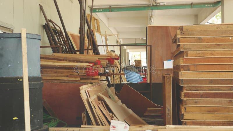 Reservado desordenado da garagem com madeiras velhas do vintage, quadros do metal e equipamentos abandonados imagem de stock royalty free