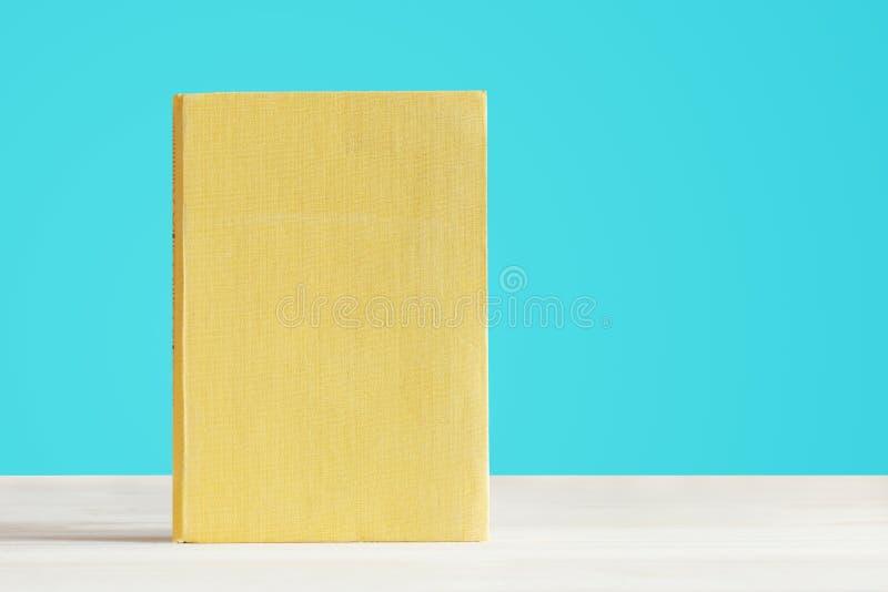 Reserve con la cubierta amarilla en blanco con un fondo azul foto de archivo libre de regalías