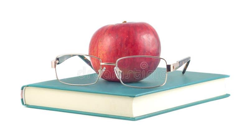 Reserve con la manzana y los vidrios rojos en un fondo blanco imágenes de archivo libres de regalías