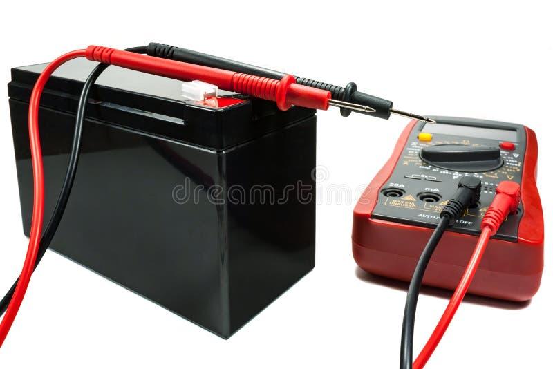 Reservebatterij met een multimeter en sondes op een witte achtergrond stock afbeelding