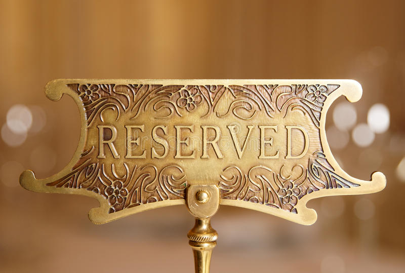 Reserved plate. Reserved brass plate on a restaurant table stock photos