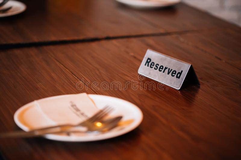 `Reserved` Sign on dining table in restaurant with spoon, fork and plate. royalty free stock photo