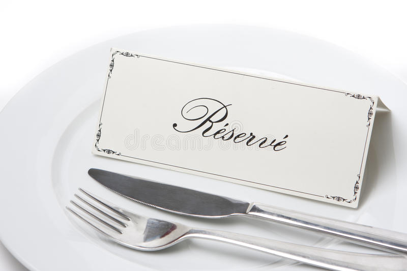 Reserved sign in french with fork and knife. Generic reserved sign on a white plate with fork and knife stock image