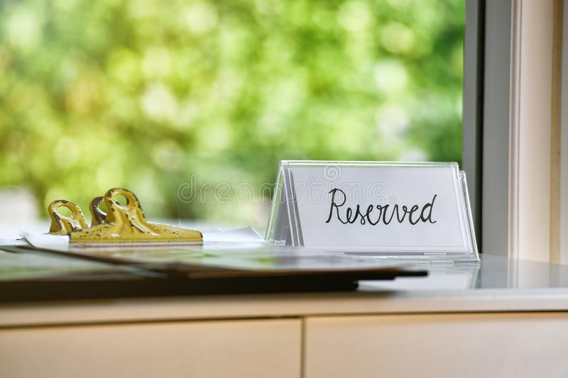Reserved sign with handwriting calligraphy style on vintage table. royalty free stock images