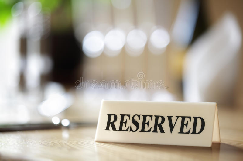 Reserved sign on restaurant table. Restaurant reserved table sign with places setting and wine glasses stock images