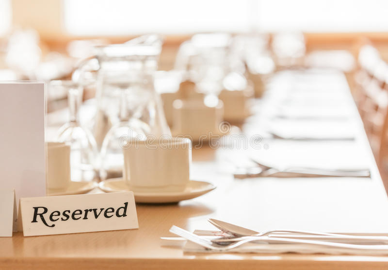 Reserved table in a restaurant. Wine glasses, coffee cups and cutlery on the table before the start of the service in the restaurant royalty free stock photos