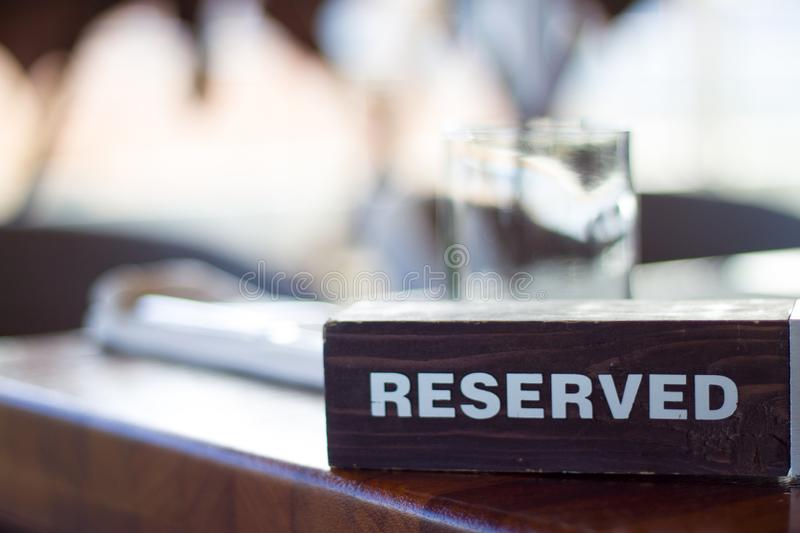 Reserved wooden Card Plate on the Table with Blurry background. Reservation Seat at restaurant. - leisure, people and service conc royalty free stock images