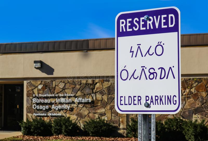 Reserverat - äldre på engelska parkeringstecken och Osage det indiska språket Wazhazhe utanför byrån av indiska angelägenheter Os royaltyfri fotografi
