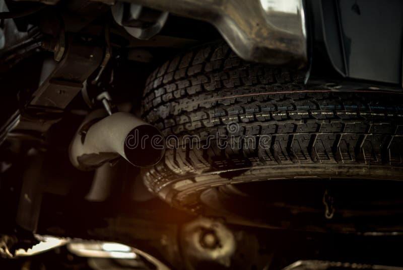 Reservereifen unter dem Auto nahe Auspuffrohr Ersatzrad Gummiprodukt Autokontrolle vor Reisekonzept stockbilder