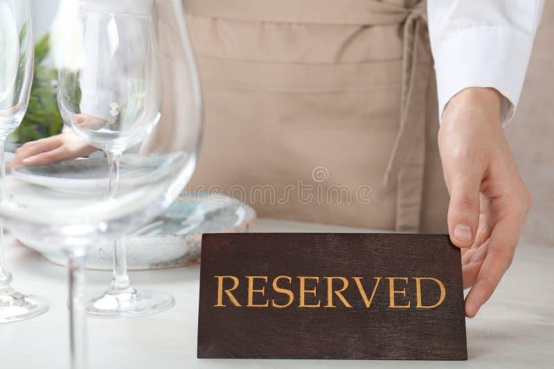 RESERVIERTES Zeichen der Kellnereinstellung auf Restauranttabelle lizenzfreies stockbild