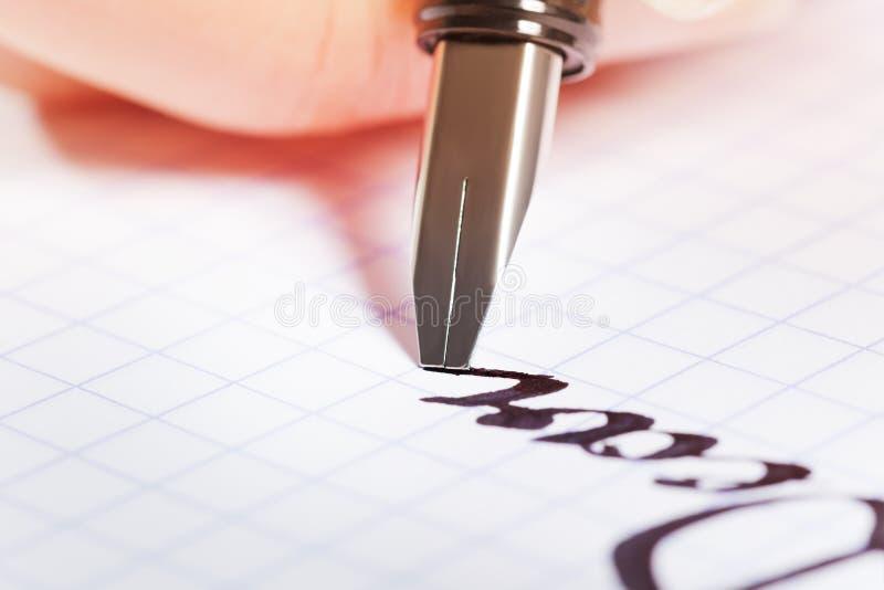 Reservoarpenna som skriver ordraringen på grafblocket arkivfoton