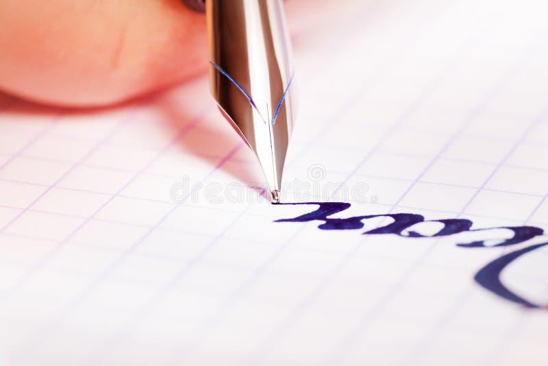 Reservoarpennahandstil på den kvadrerade anteckningsboken royaltyfri bild