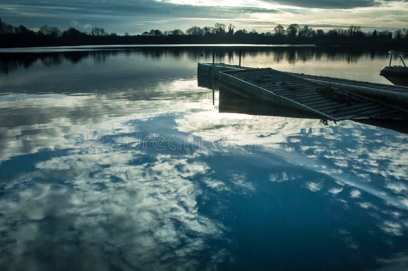 Reservoir, botenhuis en wolkenbezinningen royalty-vrije stock afbeelding