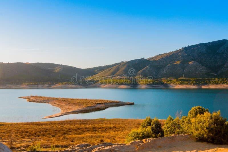 Reservoir am Fuß der Berge mit einer kleinen Insel in der Mitte stockbilder