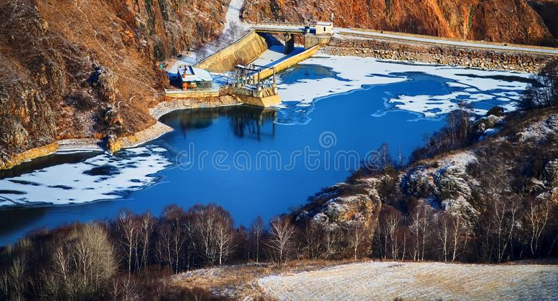 Reservoir in gorge for water supply of settlements and fields. Reservoir, dammed body of water, partially frozen in the gorge for water supply of settlements and royalty free stock photo