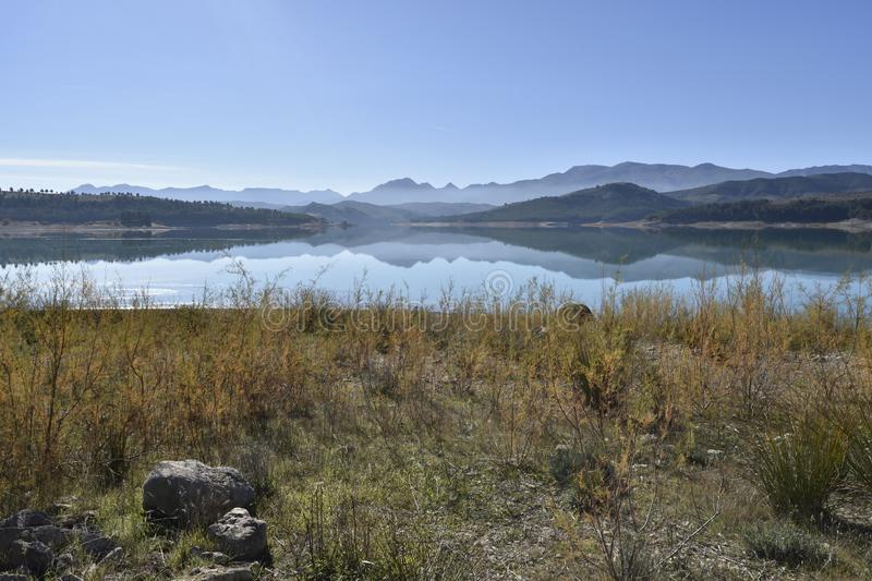 Reservoir waters with the reflection of the mountains in the water stock photo
